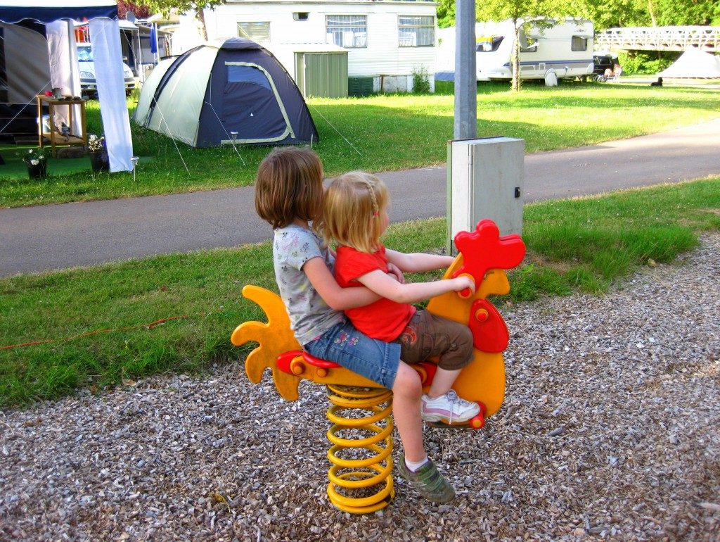 The girls riding their rooster named Chicken at the campsite